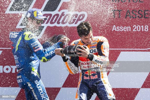 TOPSHOT Winner Marc Marquez from Spain and second placed Alex Rins from Spain celebrate on the podium during the MotoGP race of the Motorcycling...