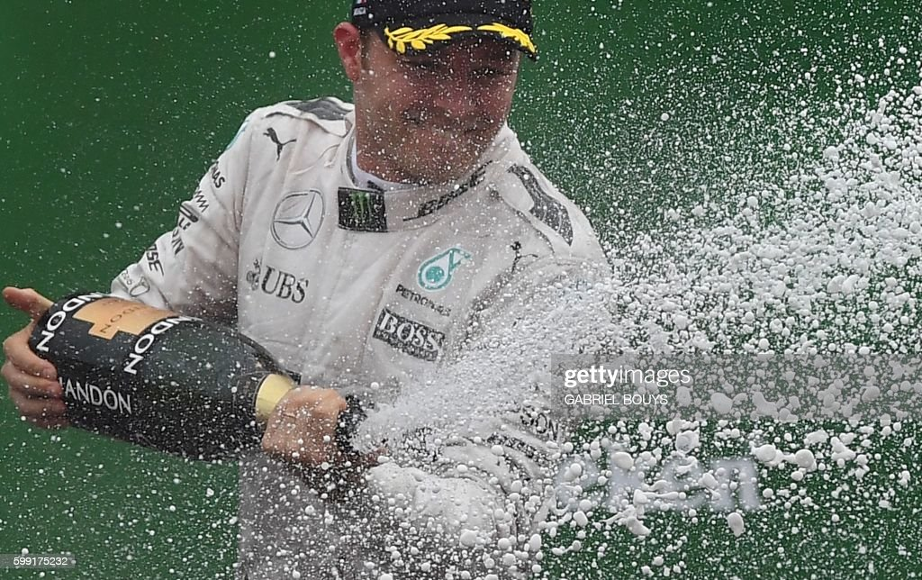 TOPSHOT - Winner Mercedes AMG Petronas F1 Team's German driver Nico Rosberg sprays champagne on the podium after the Italian Formula One Grand Prix at the Autodromo Nazionale circuit in Monza on September 4, 2016. /