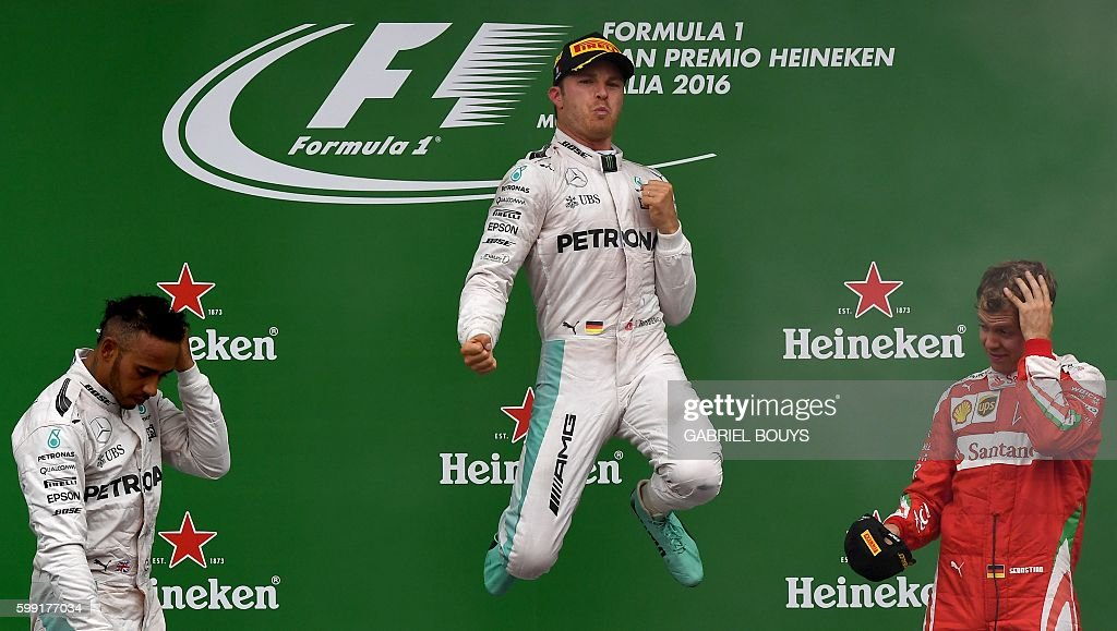TOPSHOT - Winner Mercedes AMG Petronas F1 Team's German driver Nico Rosberg (C) celebrates on the podium next to second placed Mercedes AMG Petronas F1 Team's British driver Lewis Hamilton (L) and third placed Scuderia Ferrari's German driver Sebastian Vettel following the Italian Formula One Grand Prix at the Autodromo Nazionale circuit in Monza on September 4, 2016. /