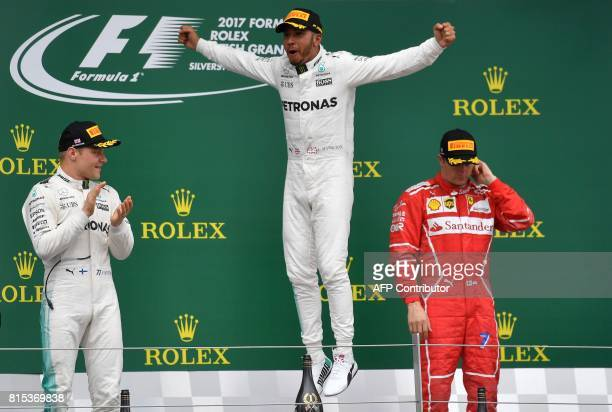 Winner Mercedes' British driver Lewis Hamilton celebrates on the podium next to second placed Mercedes' Finnish driver Valtteri Bottas and third...