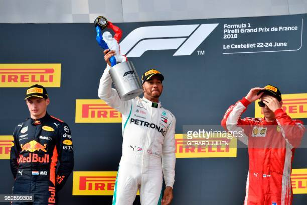 Winner Mercedes' British driver Lewis Hamilton celebrates on the podium next to second placed Red Bull Racing's Dutch driver Max Verstappen and third...