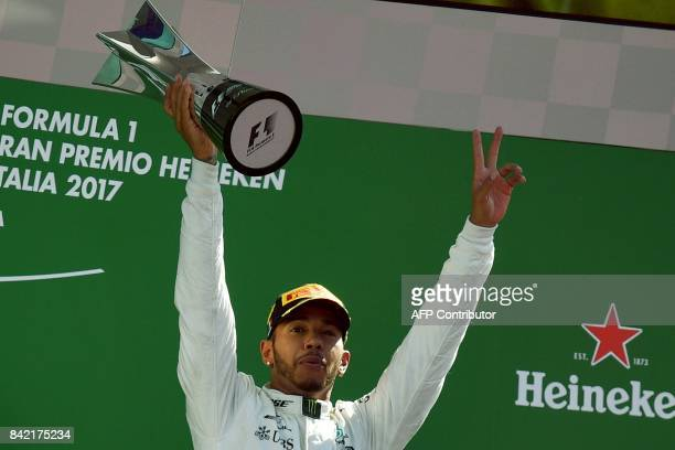 TOPSHOT Winner Mercedes' British driver Lewis Hamilton celebrates on the podium after the Italian Formula One Grand Prix at the Autodromo Nazionale...