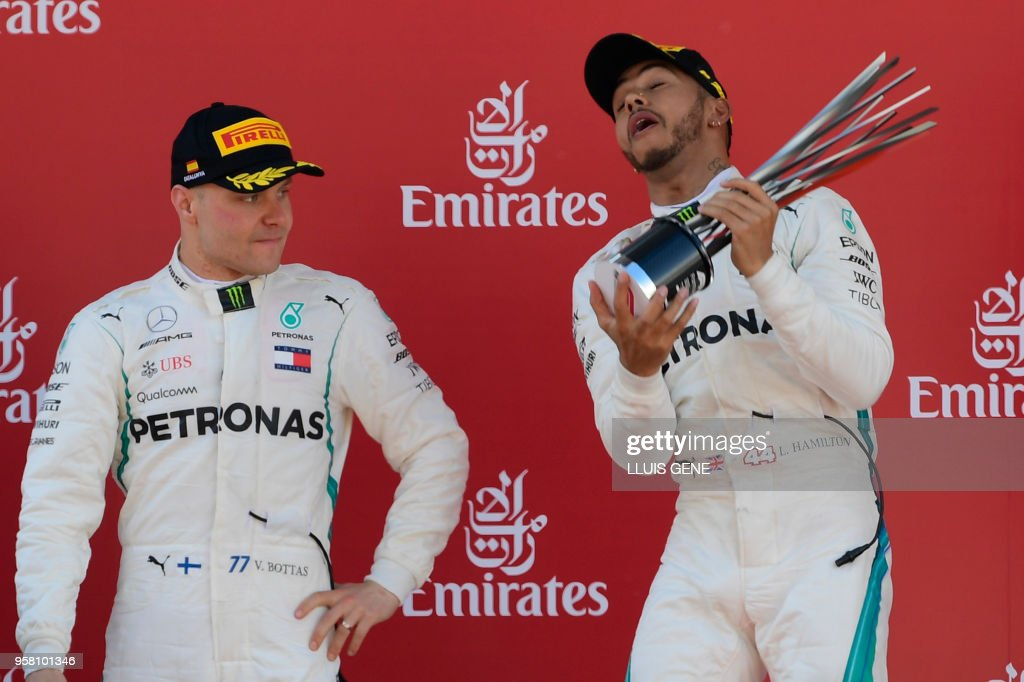 TOPSHOT - Winner Mercedes' British driver Lewis Hamilton (R) celebrates on the podium with second placed Mercedes' Finnish driver Valtteri Bottas after winning the Spanish Formula One Grand Prix at the Circuit de Catalunya in Montmelo in the outskirts of Barcelona on May 13, 2018.