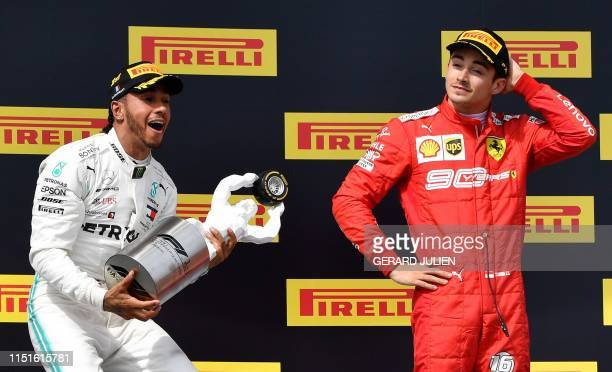 Winner Mercedes' British driver Lewis Hamilton celebrates with his trophy next to third placed Ferrari's Monegasque driver Charles Leclerc on the...
