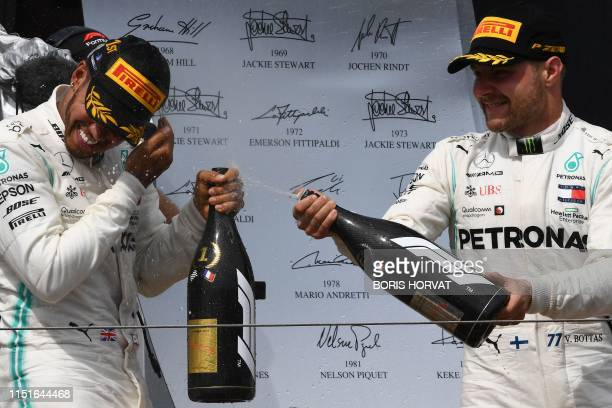 Winner Mercedes' British driver Lewis Hamilton celebrates with champagne on the podium with second placed Mercedes' Finnish driver Valtteri Bottas...