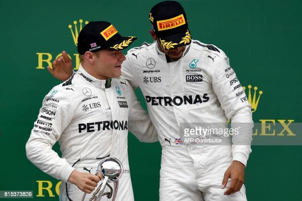 Winner Mercedes' British driver Lewis Hamilton celebrates with second placed Mercedes' Finnish driver Valtteri Bottas after the British Formula One...