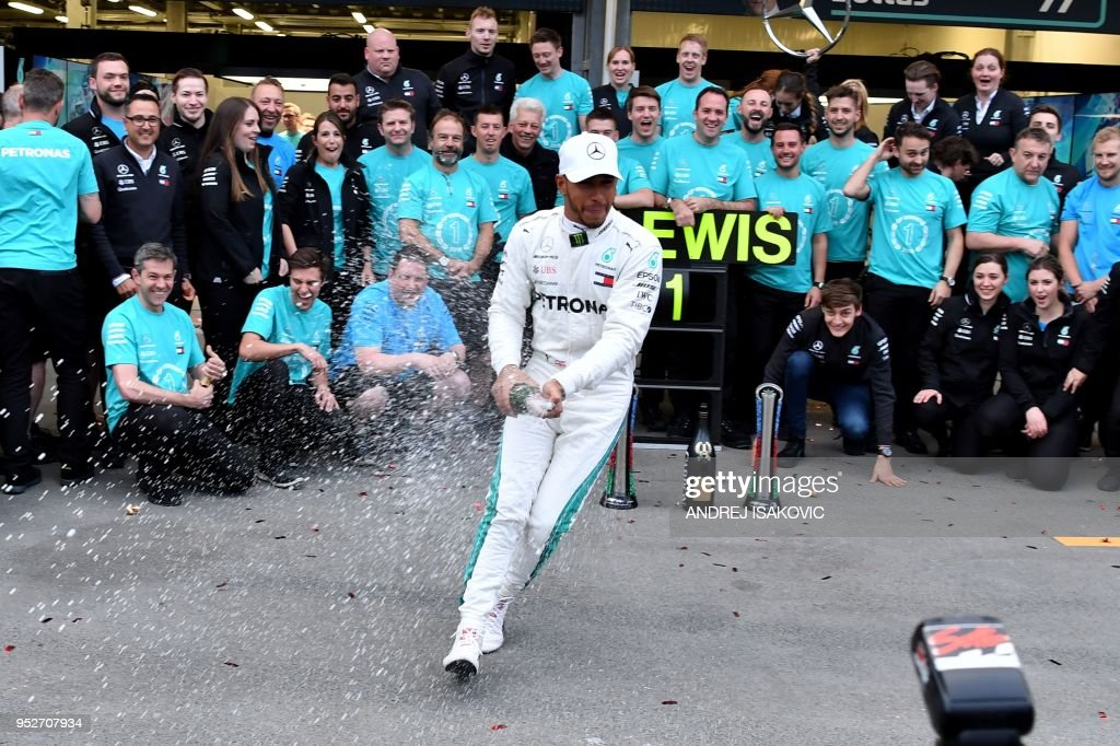 Winner Mercedes' British driver Lewis Hamilton celebrates with the team crew after the Formula One Azerbaijan Grand Prix at the Baku City Circuit in Baku on April 29, 2018.