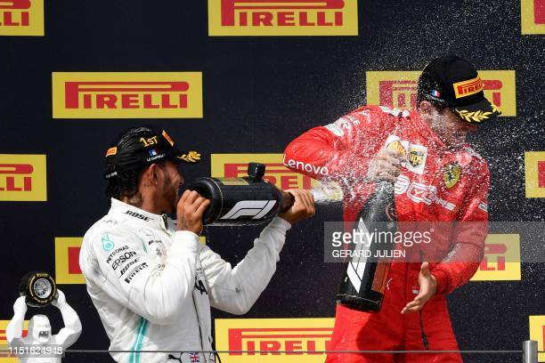 Winner Mercedes' British driver Lewis Hamilton celebrates with third placed Ferrari's Monegasque driver Charles Leclerc on the podium after the...
