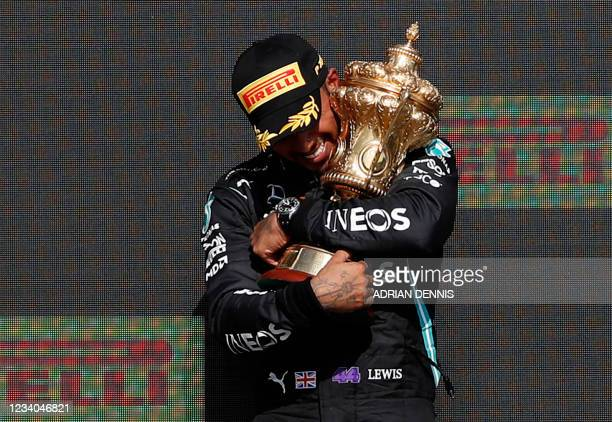 Winner Mercedes' British driver Lewis Hamilton holds the trophy on the podium after the Formula One British Grand Prix motor race at Silverstone...