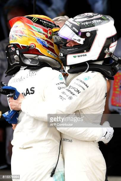Winner Mercedes' British driver Lewis Hamilton is congratulated by teammate Mercedes' Finnish driver Valtteri Bottas after the British Formula One...