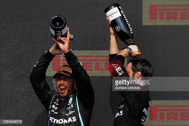 Winner Mercedes' British driver Lewis Hamilton pours champaigne over his head on the podium after the Formula One British Grand Prix motor race at...