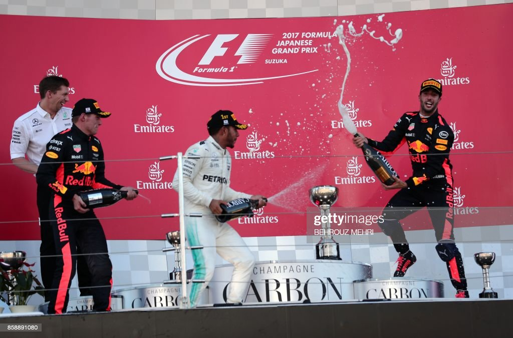 TOPSHOT - Winner Mercedes' British driver Lewis Hamilton (C), second placed Red Bull's Dutch driver Max Verstappen (front L) and third placed Red Bull's Australian driver Daniel Ricciardo (R) spray champagne on each other at the podium following the Formula One Japanese Grand Prix at Suzuka on October 8, 2017. / AFP PHOTO / Behrouz MEHRI