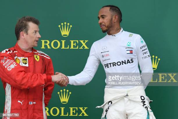 TOPSHOT Winner Mercedes' British driver Lewis Hamilton shakes hands with second placed Ferrari's Finnish driver Kimi Raikkonen as they celebrate on...