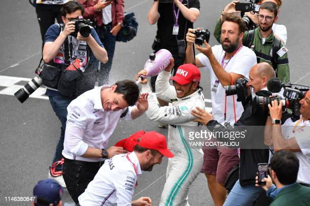Winner Mercedes' British driver Lewis Hamilton spills champagne over Mercedes AMG Petronas F1 Team's team principal Toto Wolff after the Monaco...