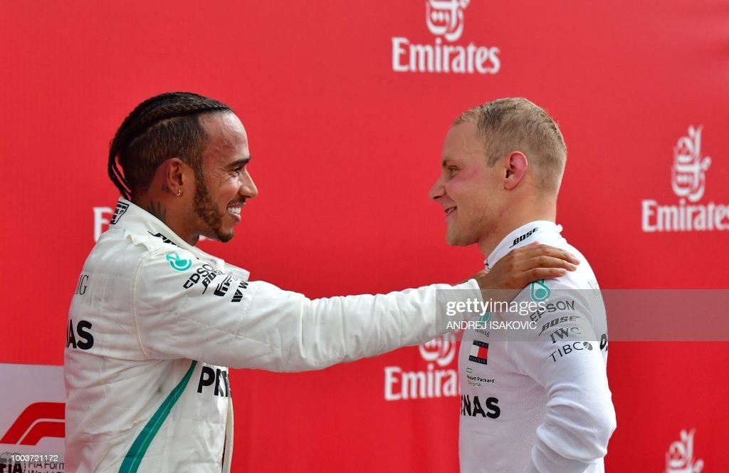 TOPSHOT - Winner Mercedes' British driver Lewis Hamilton (L) talks with second placed Mercedes' Finnish driver Valtteri Bottas after the German Formula One Grand Prix at the Hockenheim racing circuit on July 22, 2018 in Hockenheim, southern Germany.