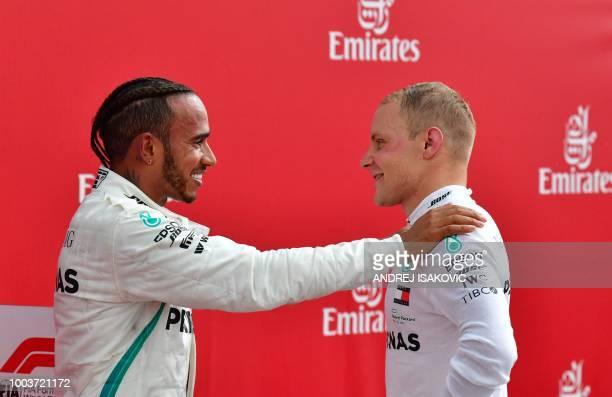 TOPSHOT Winner Mercedes' British driver Lewis Hamilton talks with second placed Mercedes' Finnish driver Valtteri Bottas after the German Formula One...