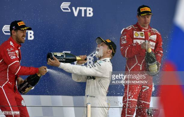 Winner Mercedes' Finnish driver Valtteri Bottas celebrates on the podium with second placed Ferrari's German driver Sebastian Vettel and third placed...