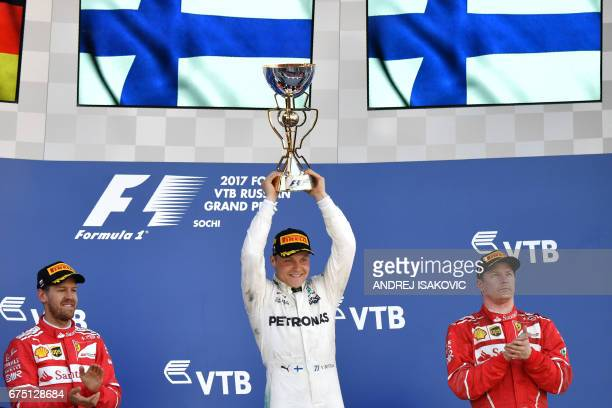 Winner Mercedes' Finnish driver Valtteri Bottas celebrates on the podium with second placed Ferrari's German driver Sebastian Vettel and third placed...