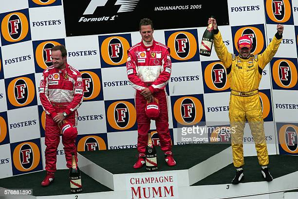 Winner Michael Schumacher, center, second place driver Rubens Barrichello, left, and third place finisher Tiago Monteiro during a subdued victory...