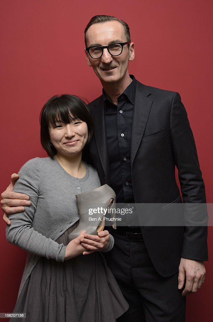 Winner Min Kyung Song (L) poses photographs with judge Bruno Frisoni (R) at the Fashion Fringe and Accessories 2012 award at IMG Fashion, on December 11, 2012 in London, England.