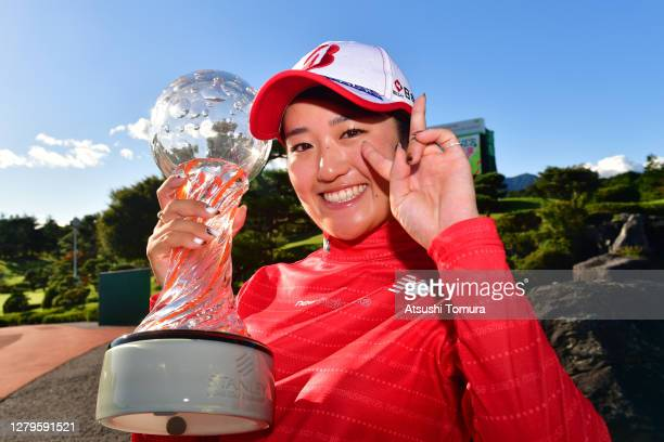Winner Mone Inami of Japan poses with the trophy after the final round of the Stanley Ladies Golf Tournament at the Tomei Country Club on October 11...