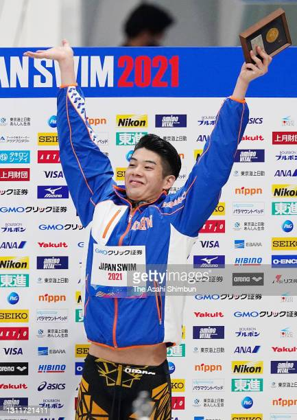 Winner Naoki Mizunuma celebrates on the podium at the medal ceremony for the Men's 100m Butterfly final on day seven of the 97th Japan Swimming...