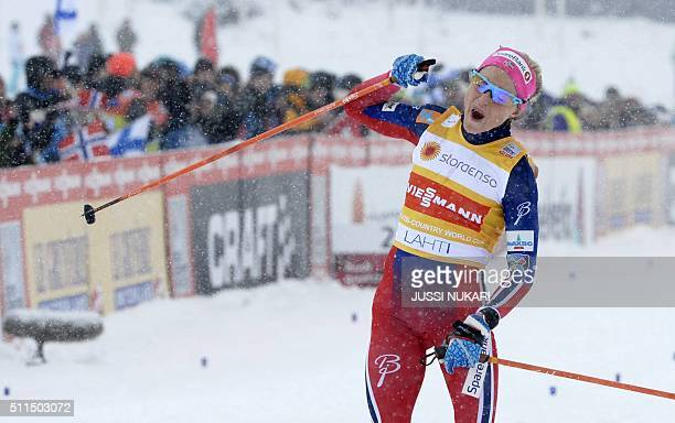 Winner Norway's Therese Johaug celebrates after the women's Skiathlon 75km classic and 75km free style event during the FIS Cross Country skiing...