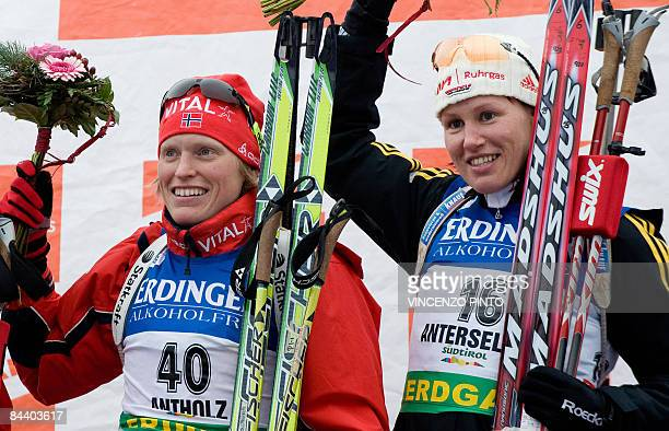 Winner Norwegian Tora Berger and third placed German Kati Wilhelm celebrate on the podium of the Women's Biathlon World Cup 75 km sprint race in...