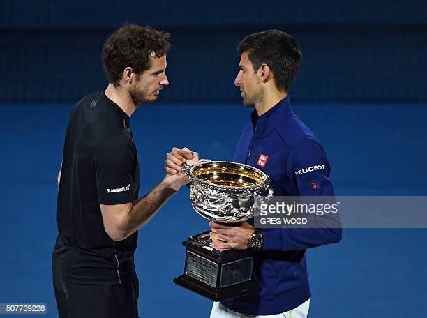 Winner Novak Djokovic of Serbia holds the winner's trophy as he shakes hands with runnerup Andy Murray of Britain at the awards ceremony after their...