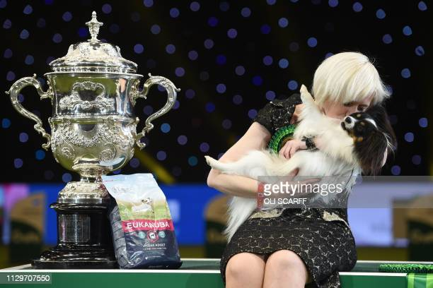 "Winner of Best in Show, the Papillon, ""Dylan"" is held by Kathleen Roosens at the trophy presentation for the Best in Show event on the final day of..."