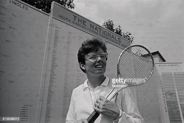 Winner of both the Wimbledon crown and the US Lawn Tennis Championship smiles through the frame of the new steel tennis racquet which is fast...