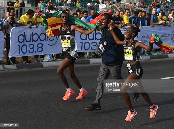 Winner of Elite Men's race Tamirat Tola and winner of Elite Women's race Worknesh Degefa of Ethiopia celebrate after Standard Chartered Dubai...
