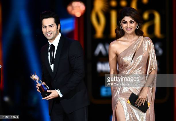 Winner of Performance in a Comic Role Varun Dhawan for 'Dishoom' accepts the award as actress Shilpa Shetty looks on during the 18th International...