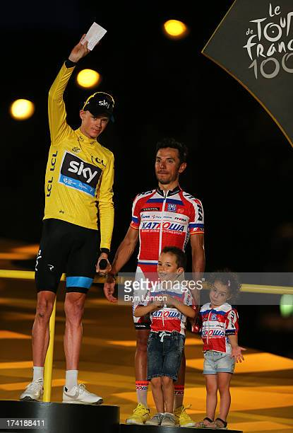 Winner of the 2013 Tour de France, Chris Froome of Great Britain and SKY Procycling celebrates on the podium alongside third placed Jouaqin 'Purito'...