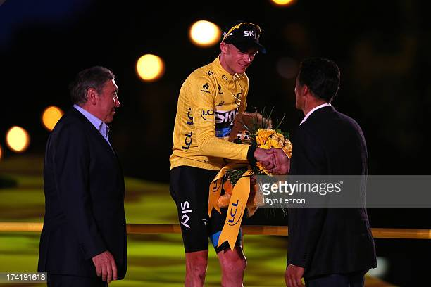 Winner of the 2013 Tour de France, Chris Froome of Great Britain and SKY Procycling is congratulated by Eddy Mercx and Miguel Indurain on the podium...