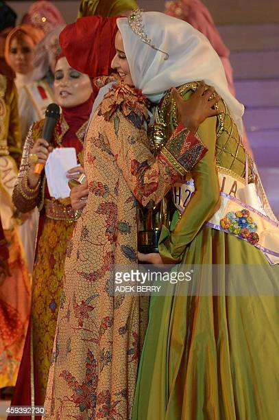 Winner of the 2014 World Muslimah Awards Fatma Ben Guefrache of Tunis is hugged by Miss Muslimah 2013 Obabiyi Aishah Ajibola of Nigeria during the...
