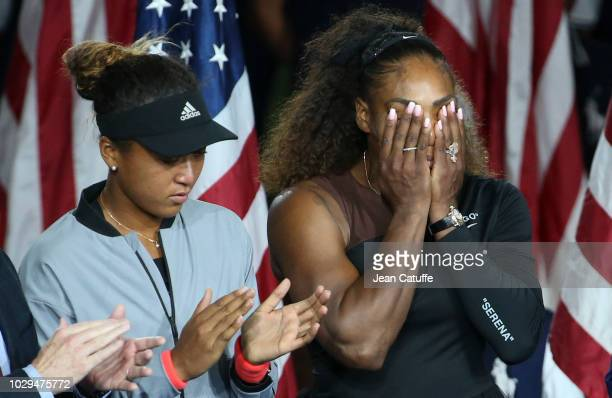 Winner of the 2018 US Open Naomi Osaka of Japan finalist Serena Williams of USA during the trophy ceremony following the women's final on day 13 of...