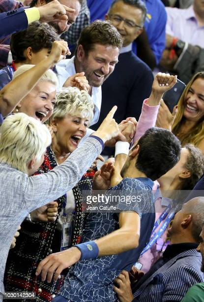 Winner of the 2018 US Open Novak Djokovic of Serbia shakes hands with his friend Gerard Butler who was in his box following the men's final on day 14...