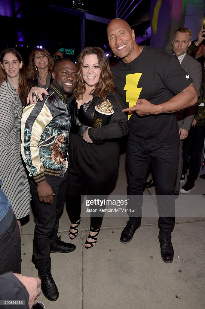 Winner of the Comedic Genius Award Melissa McCarthy (C) poses with Hosts Kevin Hart (L) and Dwayne Johnson backstage during the 2016 MTV Movie Awards at Warner Bros. Studios on April 9, 2016 in Burbank, California. MTV Movie Awards airs April 10, 2016 at 8pm ET/PT.