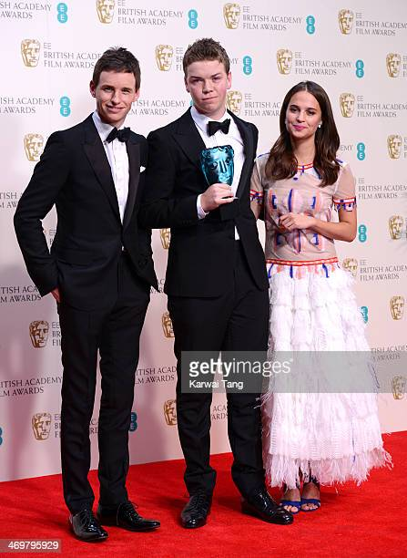 Winner of the EE Rising Star award Will Poulter poses with presenters Eddie Redmayne and Alicia Vikander in the winners room at the EE British...