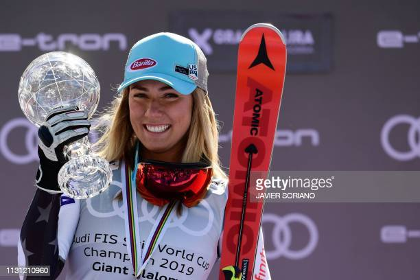 Winner of the overall FIS Alpine ski giant slalom US Mikaela Shiffrin celebres with her crystal globe trophy during the podium ceremony after...