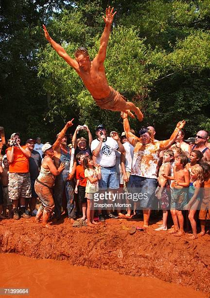 Winner of the Redneck Mud Pit Belly Flop contest Andrew Fremming of Oviedo Florida jumps off the shoulders of his friend Gene Williams to win the...