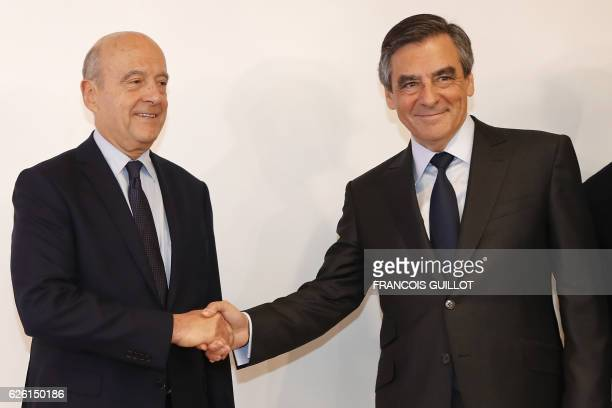 TOPSHOT Winner of the rightwing primaries ahead of France's 2017 presidential elections Francois Fillon shakes hands with mayor of Bordeaux and...