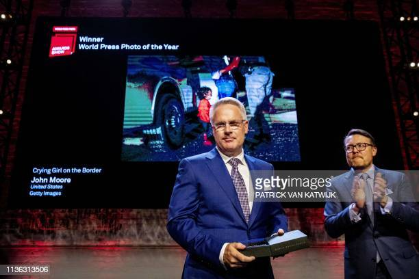 Winner of the World Press Photo 2019 Awards photographer John Moore receives the award from Dutch Prince Constantijn in front of his winning picture...