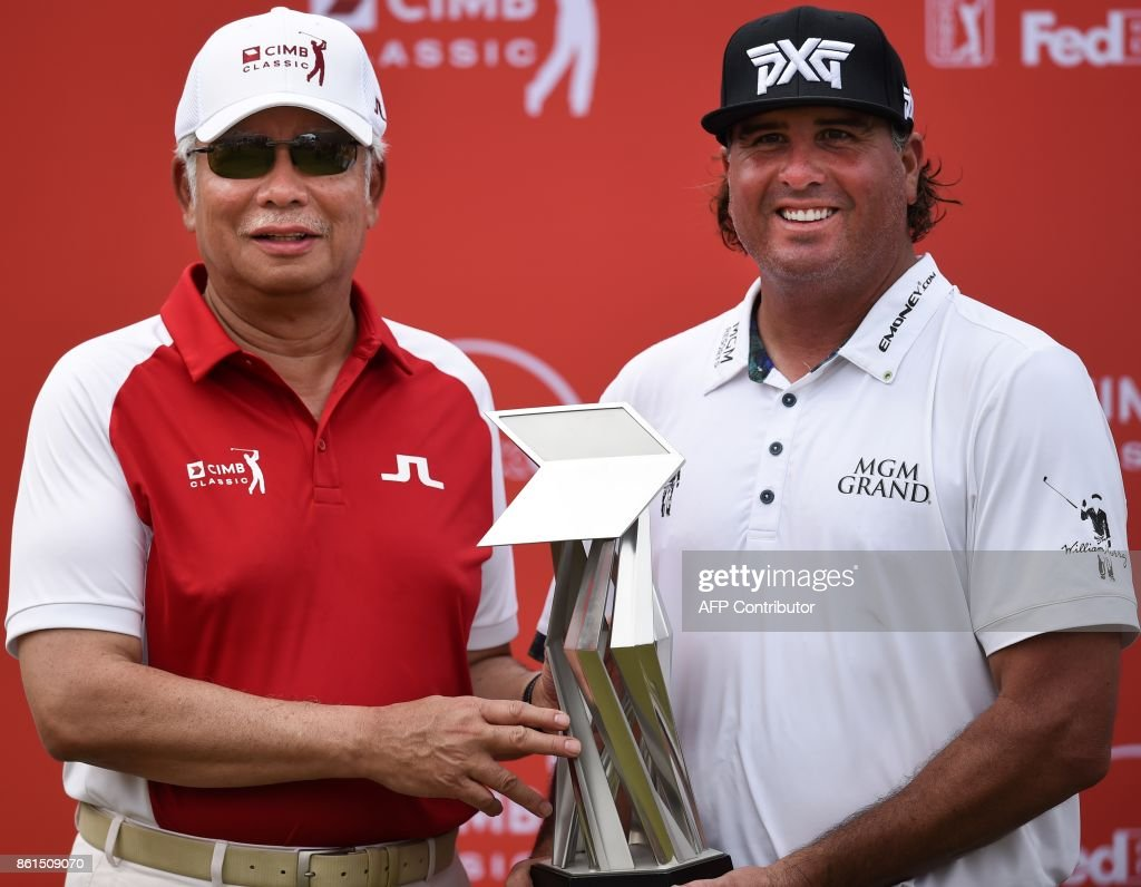 Winner Pat Perez of the US (R) and Malaysia's Prime Minister Najib Razak pose for pictures during the award ceremony after the final round of the 2017 CIMB Classic golf tournament in Kuala Lumpur on October 15, 2017. / AFP PHOTO / Mohd RASFAN