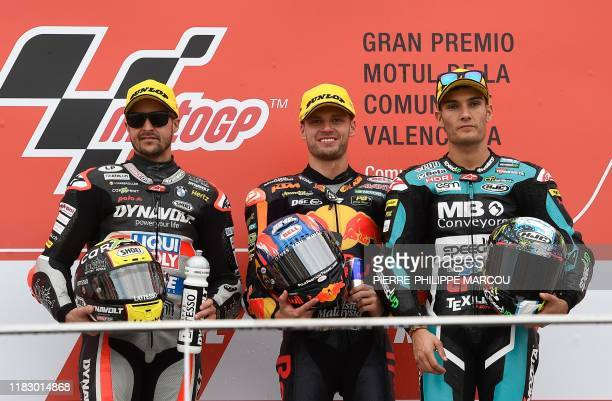 Winner Red Bull KTM Ajo's rider Brad Binder poses alongside second placed Dynavolt Intact's Swiss rider Thomas Luthi and third placed Beta Tools...