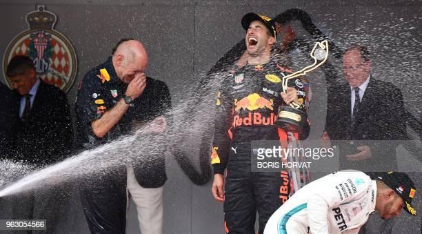 TOPSHOT Winner Red Bull Racing's Australian driver Daniel Ricciardo and Mercedes' British driver Lewis Hamilton react as they receive champagne...