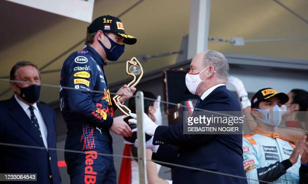Winner Red Bull's Dutch driver Max Verstappen receives the trophy from Prince Albert II of Monaco during the podium ceremony after the Monaco Formula...