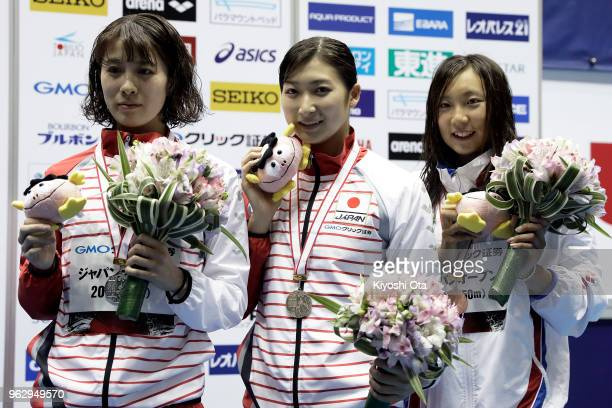 Winner Rikako Ikee of Japan celebrates with runnerup Yui Ohashi of Japan and thirdplaced Ai Soma of Japan after the Women's 100m Butterfly final on...