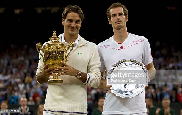 Winner Roger Federer of Switzerland and runner up Andy Murray of Great Britain hold their trophies after their Gentlemen's Singles final match on day...